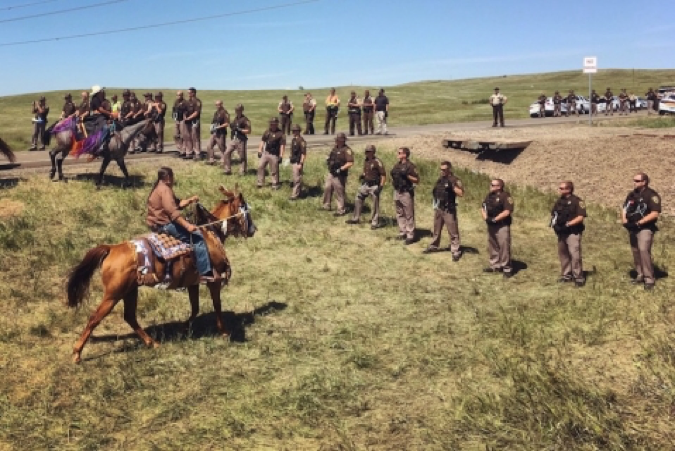 water protector on a horse with dancers while a line of police looks on