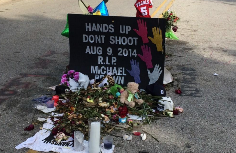 a shrine contrsucted in the middle of a street with candles, flowers, a teddy bear, a sports jersey, and other items | hands up don't shoot. aug 9, 2014, R.I.P. Michael Brown